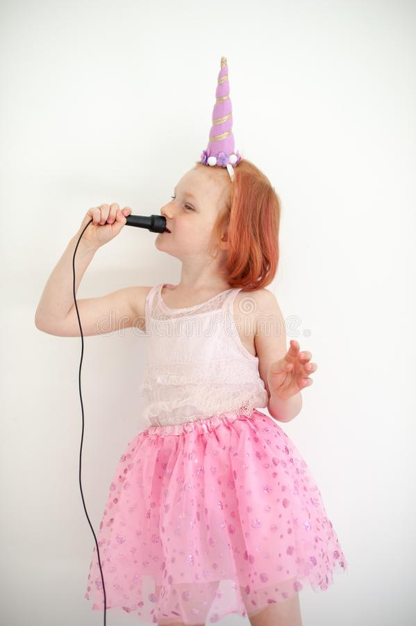 独角兽服装的一个女孩唱歌入话筒 库存图片