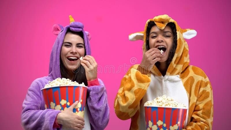 独角兽的吃玉米花和观看喜剧的两名妇女和长颈鹿睡衣 库存照片