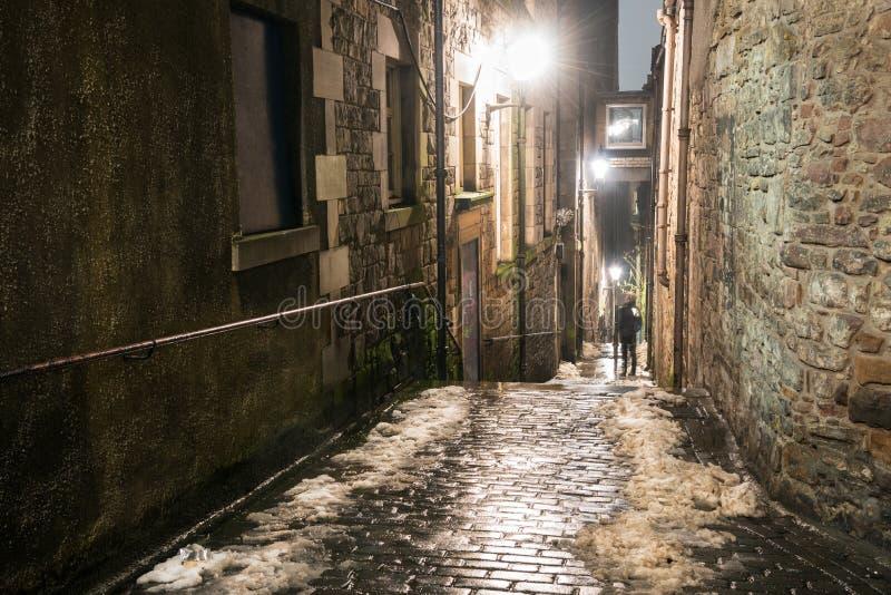狭窄在老石大厦之间的被修补的楼梯在晚上 免版税库存图片