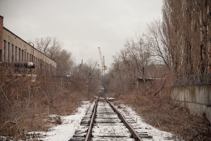 狭窄测量仪铁路在工业区 与雾的降雪 免版税库存图片