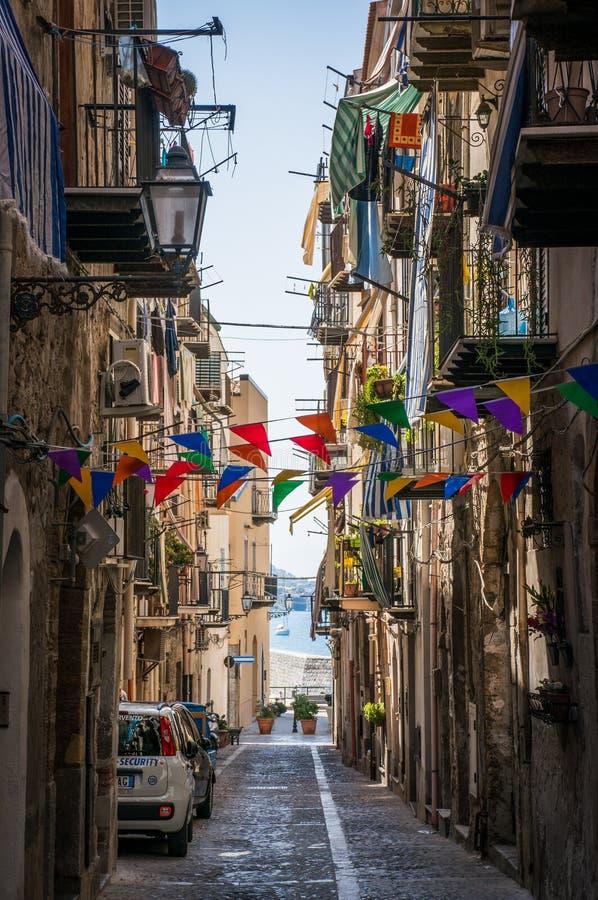 狭窄的意大利街道在Cefalu镇 免版税库存照片