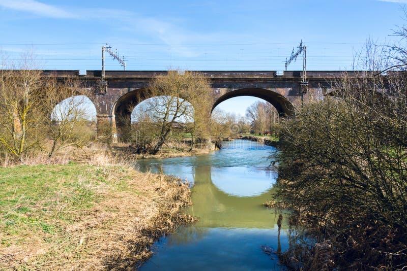 狭窄的河在铁路桥下在早期的春天- 1 免版税库存照片