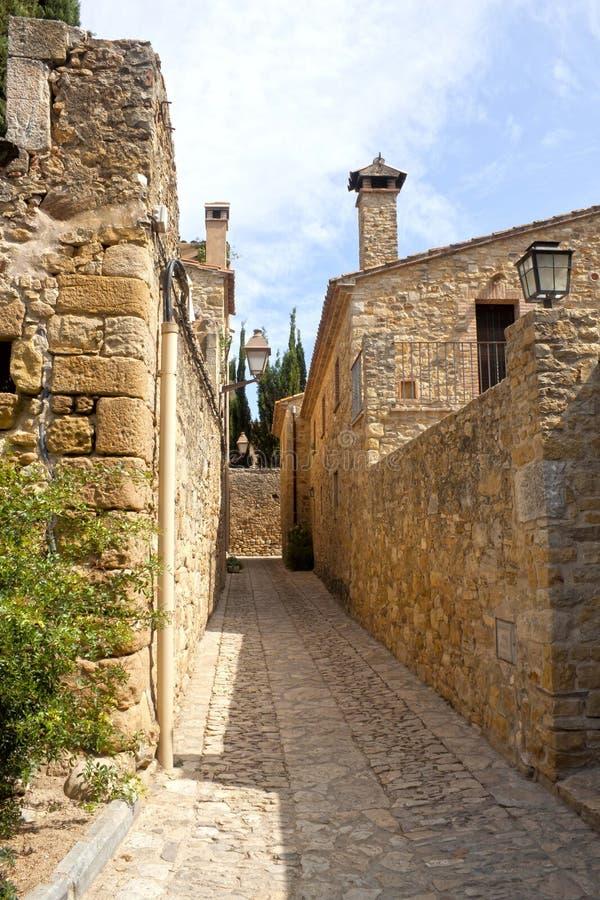 狭窄的街道、石路面和清楚的天空在Peratallada 库存照片