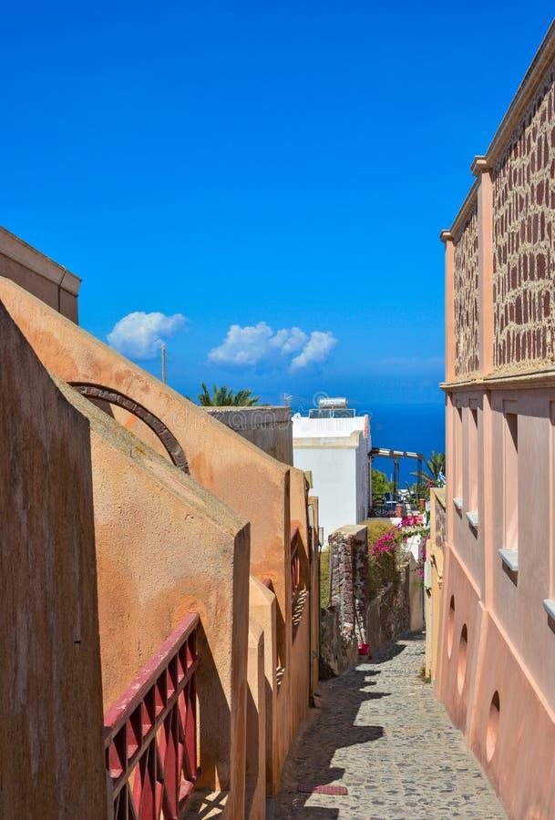 狭窄的街道在Oia,圣托里尼,海视图。 免版税库存图片