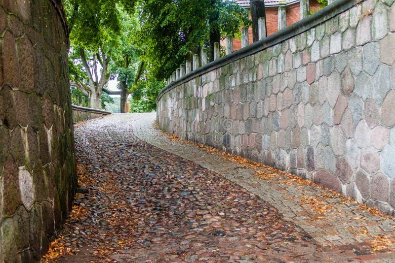 狭窄的陡峭的被修补的胡同在考纳斯,Lithuan 库存图片