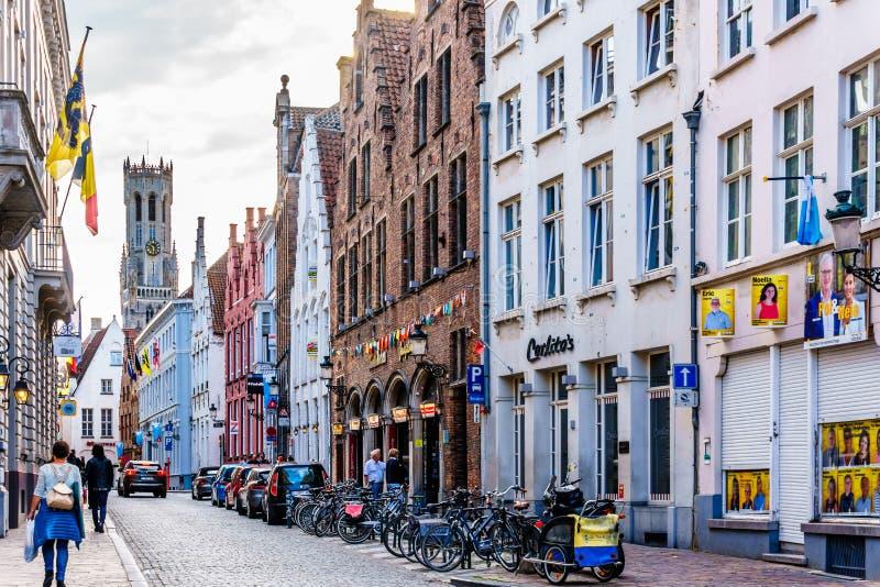 狭窄的鹅卵石街道和砖房子有步山墙的和钟楼塔在背景中在布鲁日,比利时  免版税库存图片
