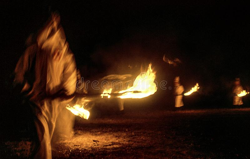 狭长的土地,佛罗里达,美国-大约1995年-三K党KKK夜白色长袍的,烧火炬的敞篷仪式成员 免版税库存照片