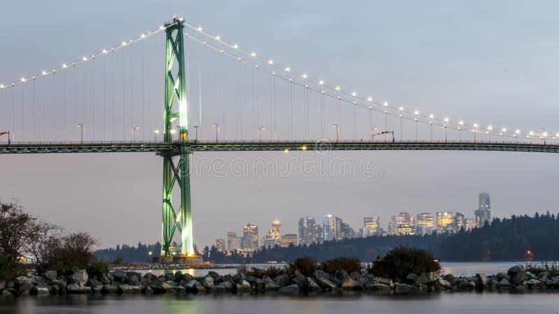 狮子在日落的门桥梁与温哥华在背景中 免版税库存照片