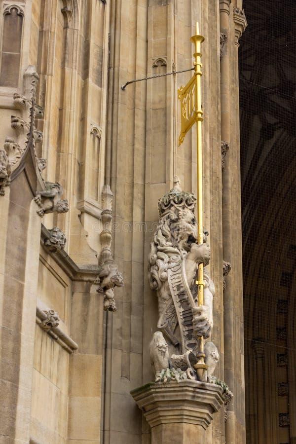 狮子在皇家入口前守卫在维多利亚塔下在英国议会大厦在伦敦,英国 图库摄影