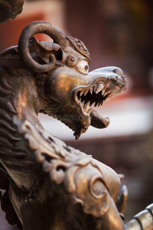 狮子由古铜制成,在古老佛教寺庙 免版税库存照片