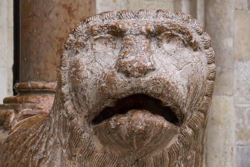狮子雕塑与在中央寺院前面祈祷在摩德纳,意大利 免版税库存图片