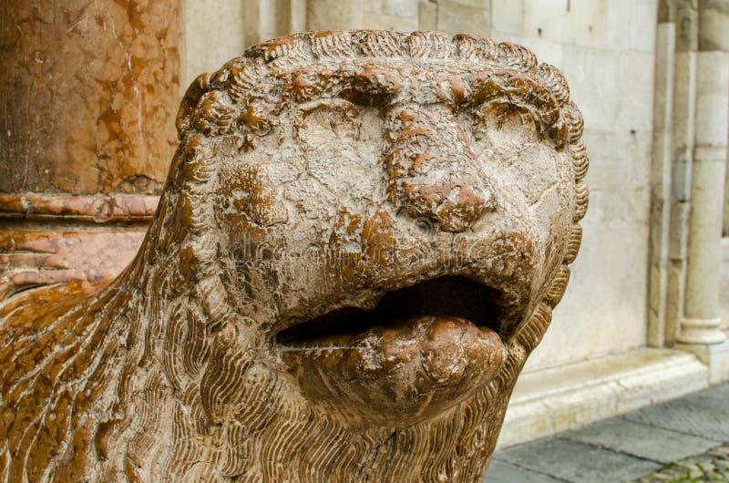 狮子雕塑与在中央寺院前面祈祷在摩德纳,意大利 免版税库存照片