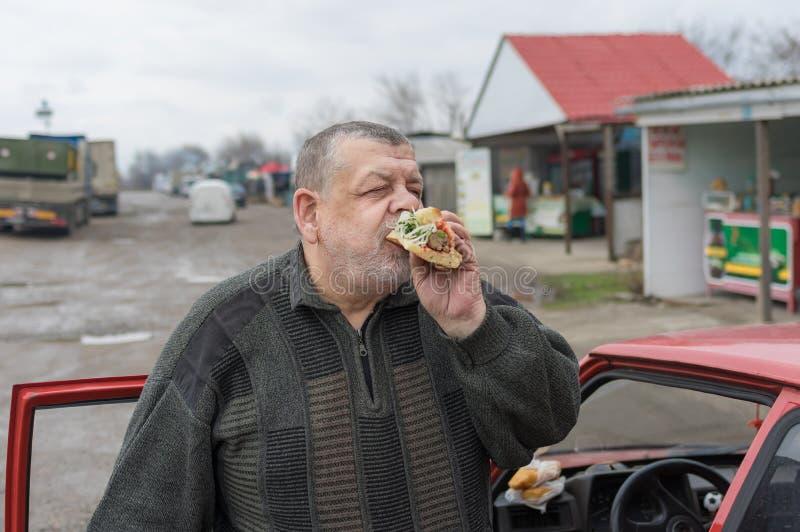 狼吞虎咽在lavash的司机lyulya kebab在他的汽车附近 免版税库存照片