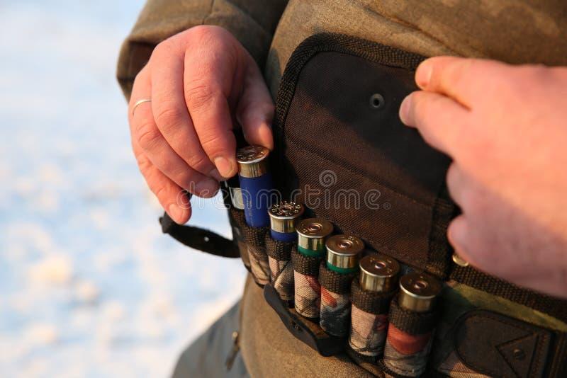 猎人去掉从子弹带关闭的一个猎人弹药筒看法 免版税库存照片
