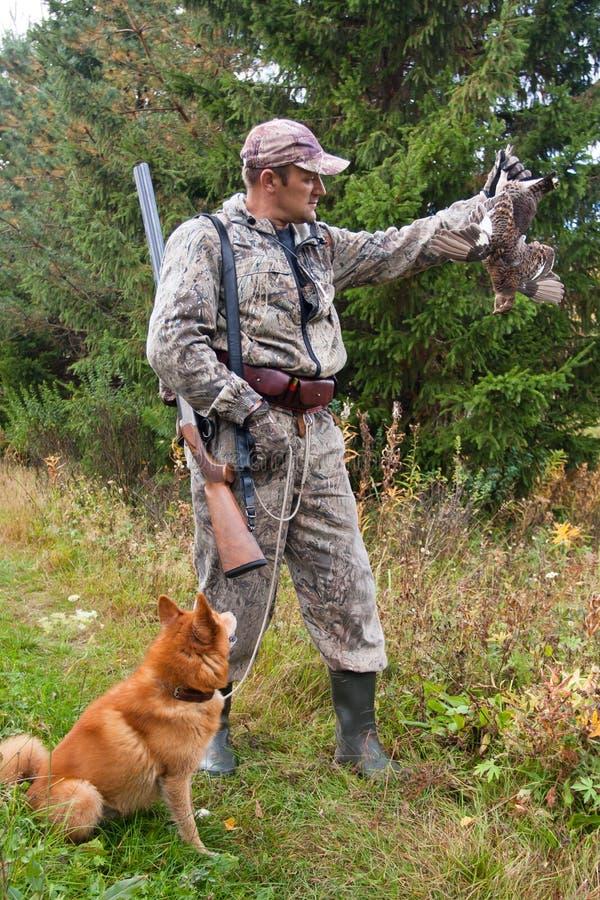 猎人和狗与狩猎战利品 库存照片