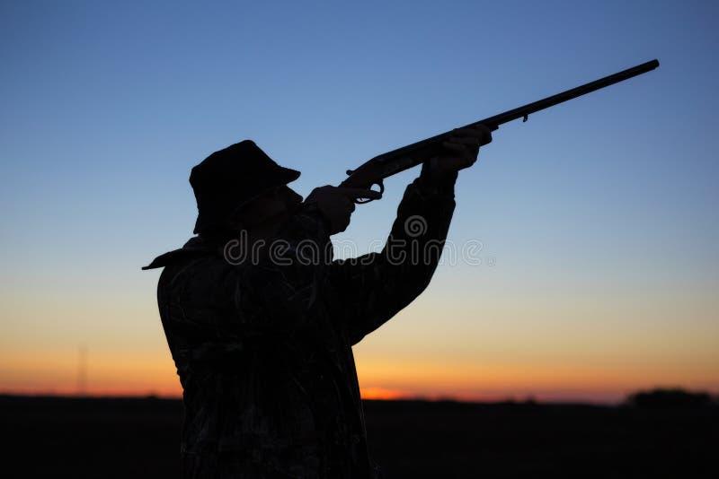 猎人在日落的` s剪影 免版税库存图片