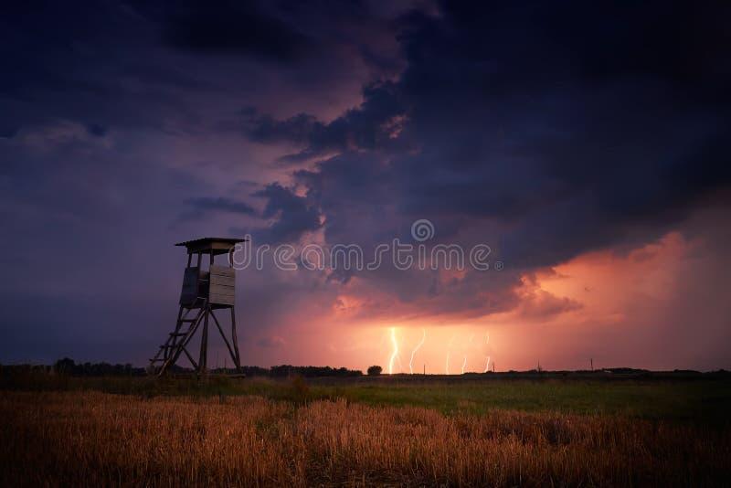 猎人在风雨如磐的领域的` s埋伏 免版税图库摄影