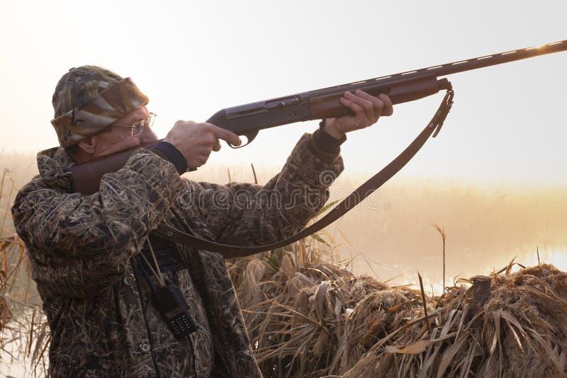 猎人射击一杆枪在黎明 图库摄影