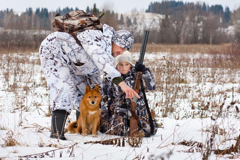 猎人显示动物他的儿子踪影  免版税库存照片