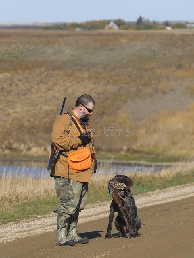 猎人用野鸡和他的狗 免版税库存图片