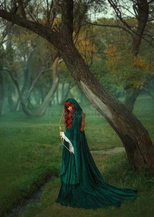 猎人,有一把弓的红发女孩在寻找受害者的手上,打扮在绿色鲜绿色velor天鹅绒礼服和a 库存照片