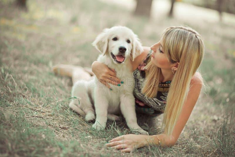 猎犬小狗可爱的场面beautifull白肤金发的夫人妇女喜欢摆在与最好的朋友狗象牙白色拉布拉多的夏时假期 图库摄影
