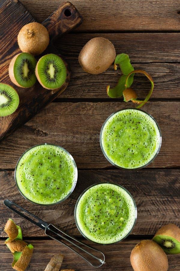 猕猴桃菠菜叶子和新鲜水果圆滑的人饮料在木土气桌,健康戒毒所饮食上 免版税库存照片