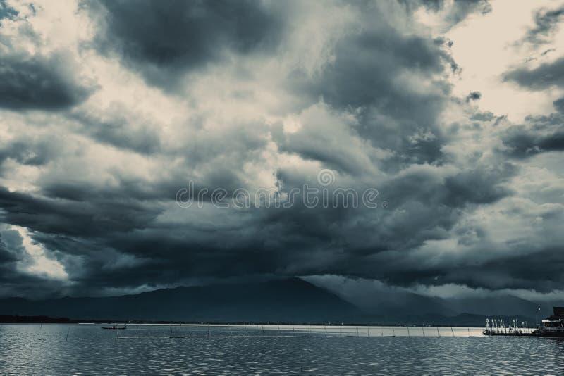 猛冲下雨在与湖的山的多云天空 免版税图库摄影