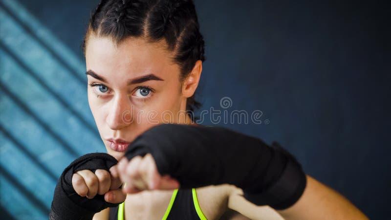 猛击在健身房的特写镜头画象美好的年轻拳击妇女训练 库存图片