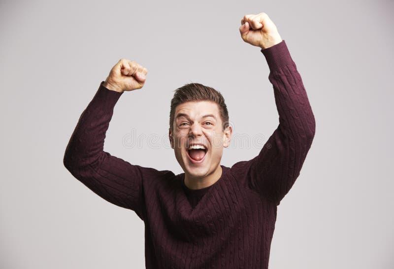 猛击空气的一名庆祝的年轻白人的画象 免版税图库摄影