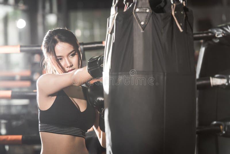 猛击与拳击手套的美丽的女性一个袋子在健身房 免版税库存照片