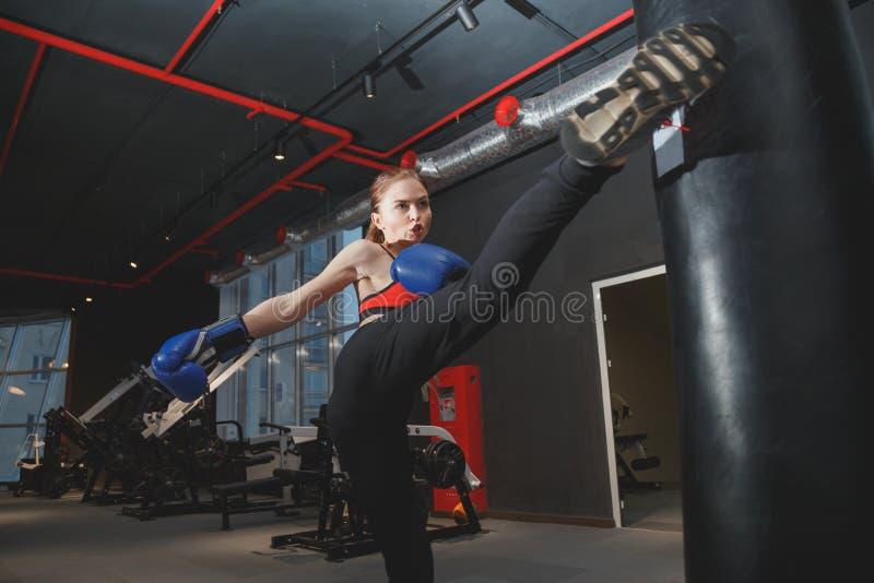 猛击Kickboxing的妇女踢袋子在健身房 图库摄影