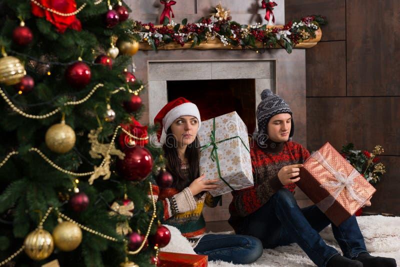 猜测在他们的圣诞节礼物的逗人喜爱的年轻对拿着boxe 库存照片