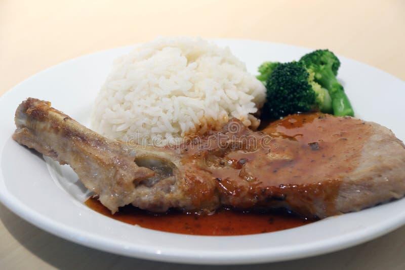 猪排牛排白米和绿色硬花甘蓝在盘在木桌上 免版税图库摄影