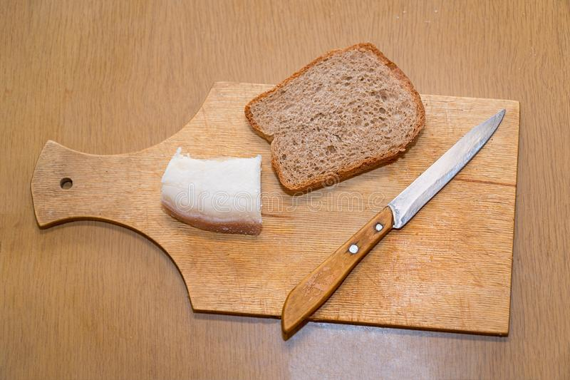 猪油、刀子和黑麦面包在切板 库存照片