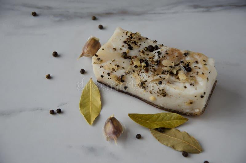 猪油鲜美片断用胡椒、海湾叶子和garlinc在白色桌上在厨房里 库存照片