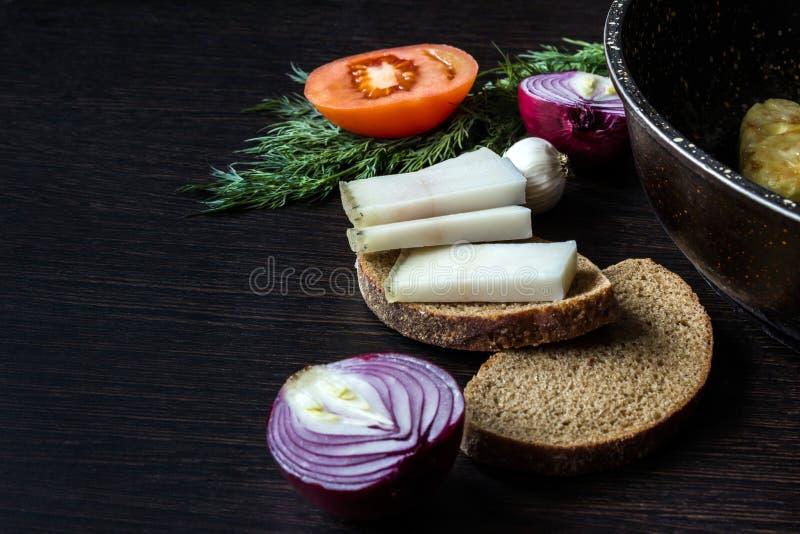 猪油salo用面包用在蕃茄的背景的红洋葱用大蒜和莳萝和平底锅在木桌上 库存照片