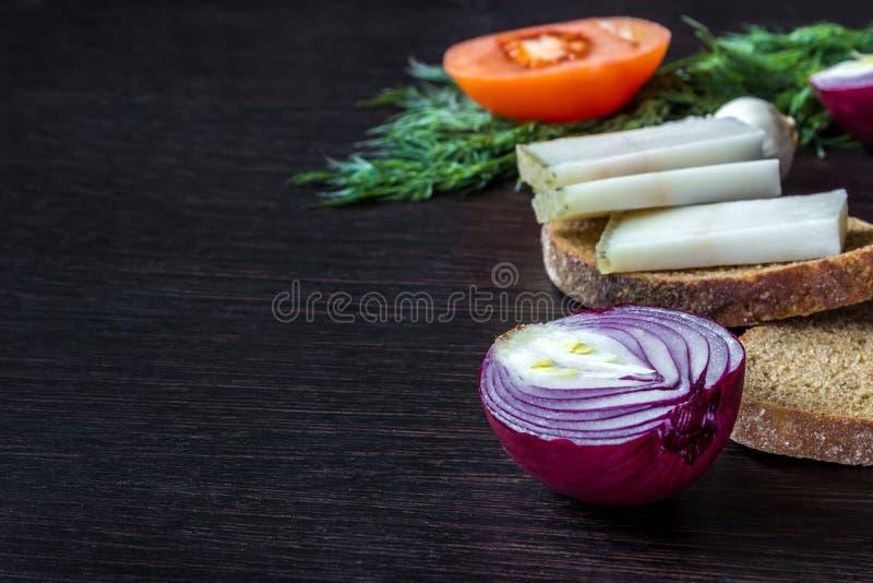 猪油salo用面包用在蕃茄的背景的红洋葱用大蒜,在木桌上的莳萝 免版税库存照片