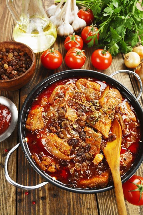 土豆炖煮的木瓜用蕃茄和葡萄干猪肉食物图片