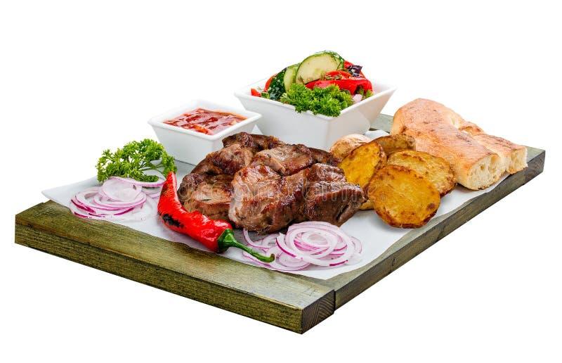 猪肉烤肉串用菜沙拉、土豆和调味汁 免版税图库摄影