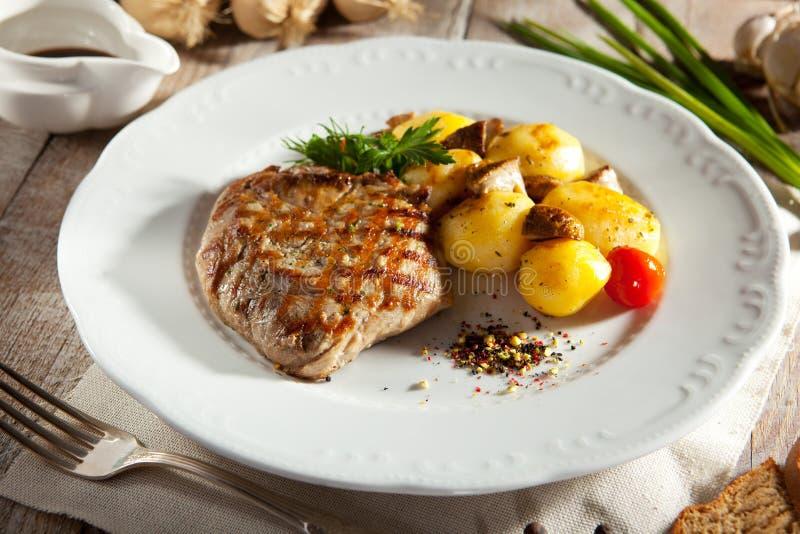 猪肉牛排用土豆 免版税图库摄影