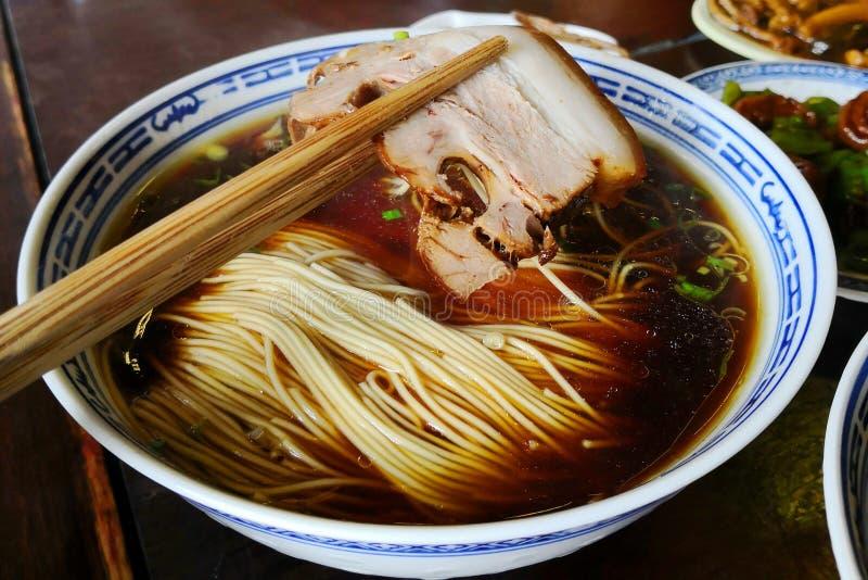 猪肉由筷子整理了有中国风格面条背景 图库摄影