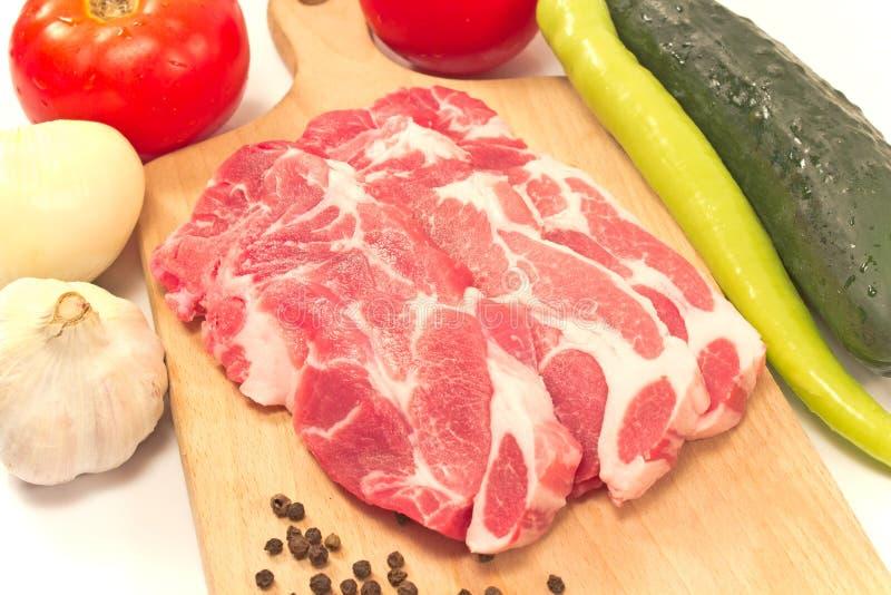 猪肉脖子与未加工的蔬菜的剁肉在切板 库存照片