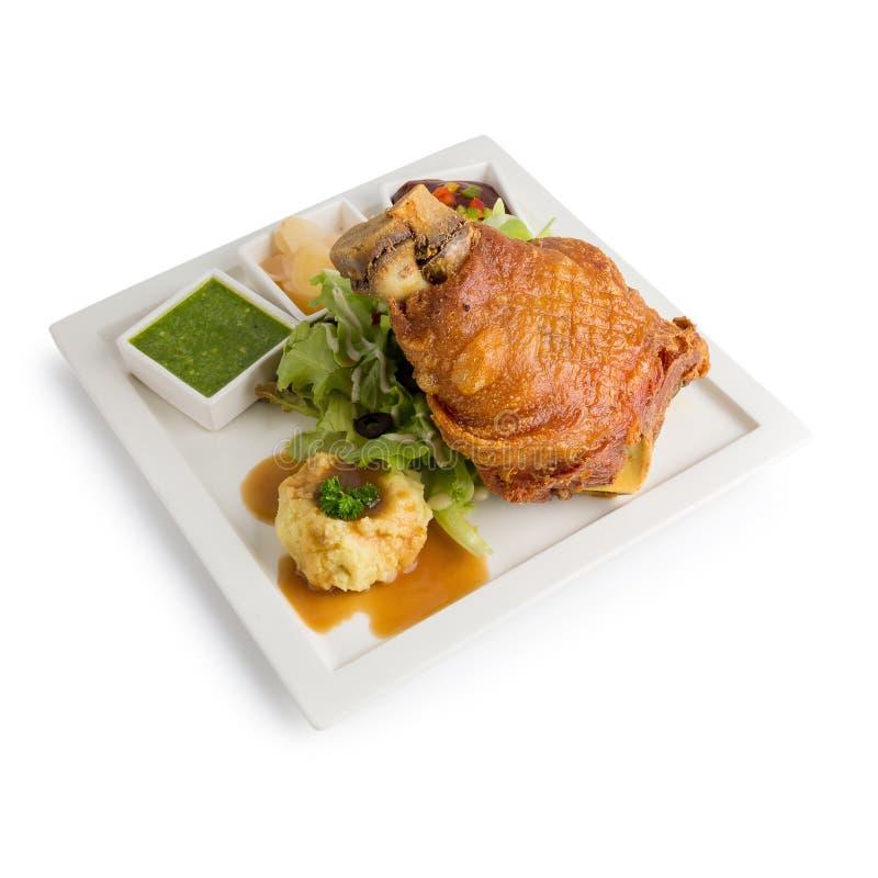 猪肉飞腓节用德语用在白色隔绝的调味汁可口食物 库存图片