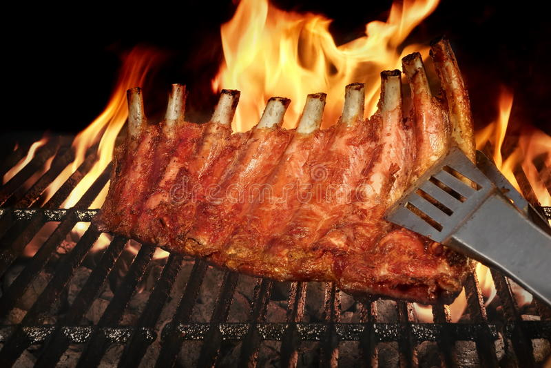 猪肉婴孩后面或排骨在BBQ格栅与火焰 免版税库存照片