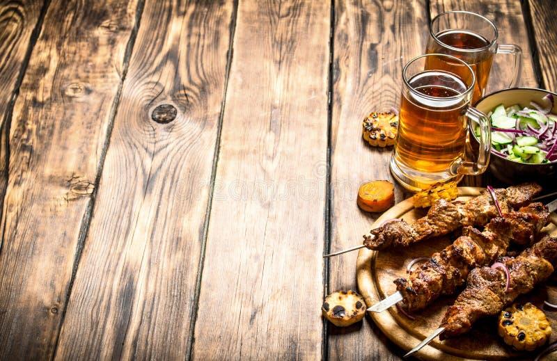 猪肉kebab用啤酒和菜 库存照片