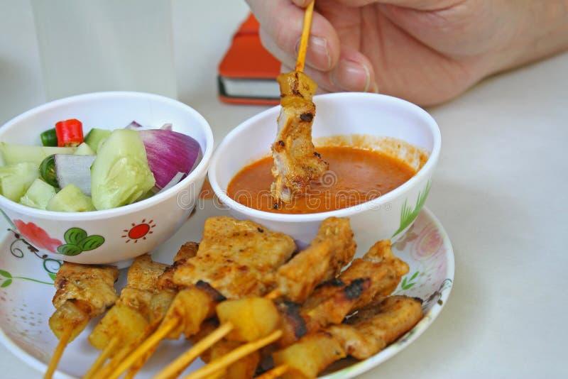 猪肉Satay用花生调味汁,是黄瓜切片和葱在醋的腌汁 库存图片