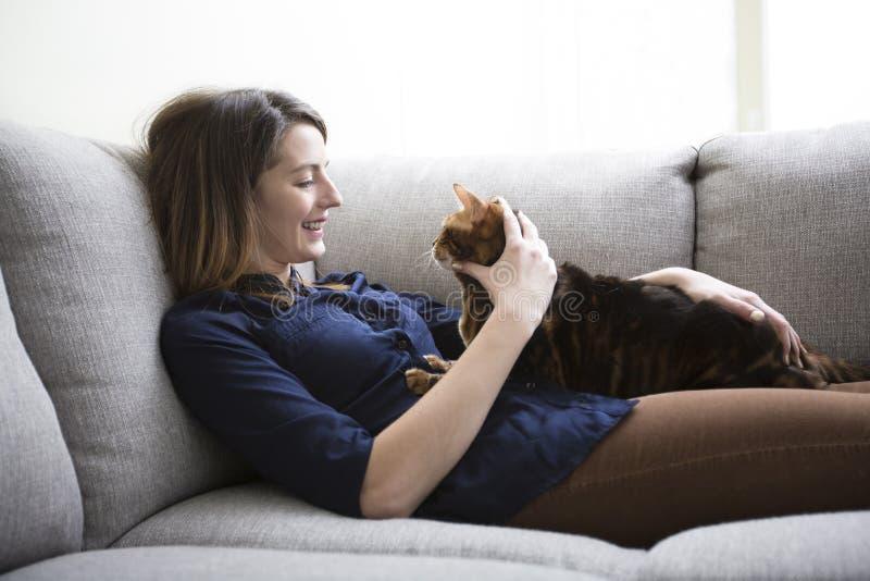 猫和妇女在长沙发的客厅 图库摄影