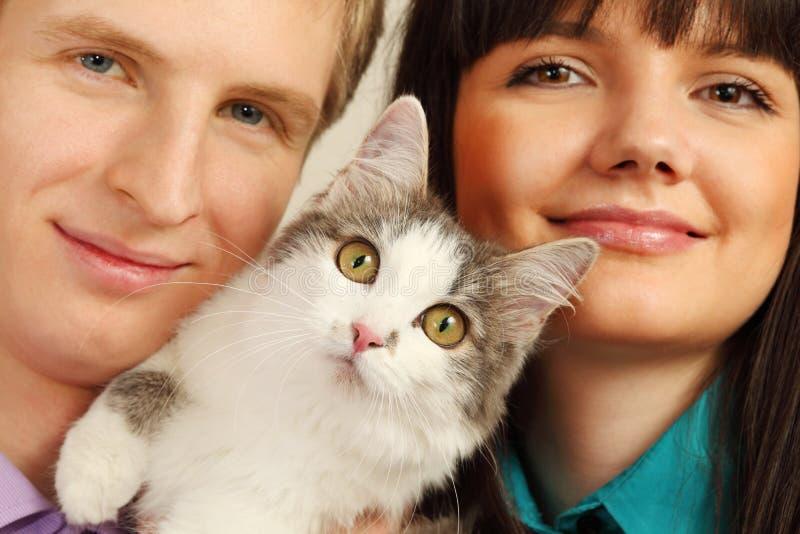 猫暂挂丈夫微笑的惊奇的妻子 免版税库存图片