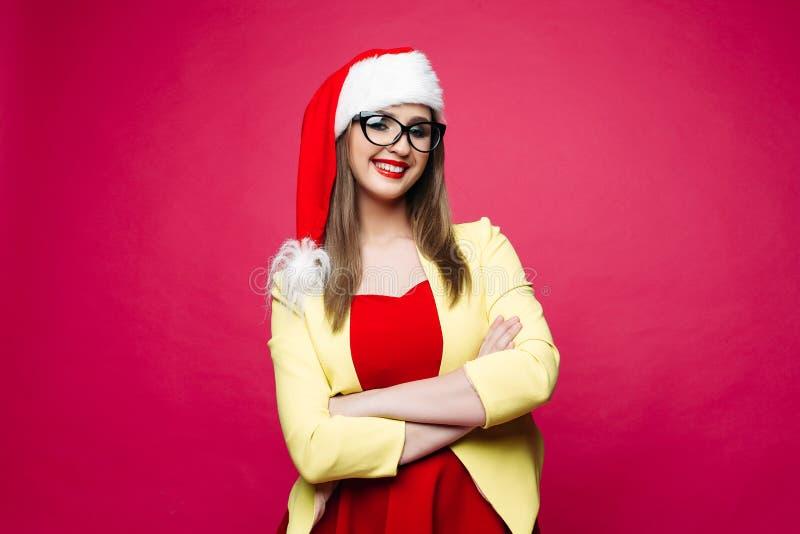 猫眼睛玻璃和圣诞老人帽子的微笑的快乐的俏丽的女孩 免版税库存图片